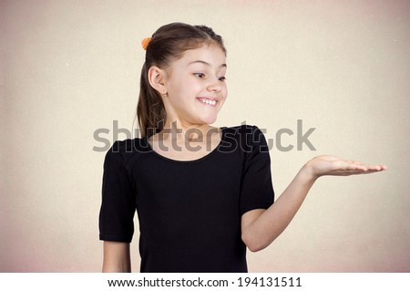 Closeup portrait happy pretty confident young smiling little girl gesturing to space right with palm up isolated light brown background. Positive human emotion signs symbol facial expression feeling - stock photo