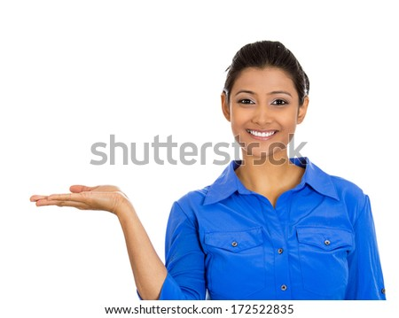 Closeup portrait happy pretty confident young smiling woman gesturing, presenting space at left with palm up isolated white background. Positive human emotion signs symbol, facial expression feelings