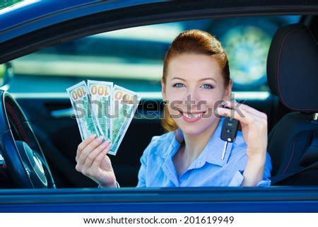 Closeup portrait happy smiling attractive woman sitting in her new black car showing keys, holding dollar bills isolated city street dealership lot background. Personal transportation purchase concept - stock photo