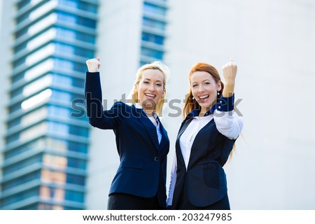 Closeup portrait happy smiling businesswomen with arms raised up, ecstatic business partners looking at camera, excited pumping fists celebrating isolated background corporate office. Positive emotion - stock photo