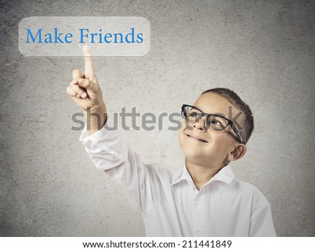 Closeup portrait happy smiling child touching, pressing make friends button icon on touchscreen display isolated grey background. Positive face expression emotion life perception. Social media concept - stock photo