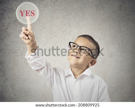 Closeup portrait happy, smiling child touching red button Yes on a touchscreen display, isolated grey background. Positive human face expression, emotions life perception. Education e-learning concept - stock photo
