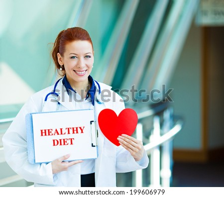 Closeup portrait happy smiling female health care professional, woman family doctor, cardiologist with stethoscope holding sign healthy diet, heart isolated hospital hallway background. Patient plan - stock photo