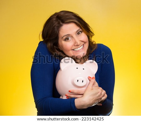 Closeup portrait happy smiling middle aged business woman holding piggy bank excited to save cash isolated yellow background. Financial savings, banking concept. Positive emotion face expression - stock photo