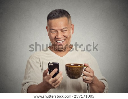 Closeup portrait happy, smiling middle aged man reading good news on smart phone, holding mobile, drinking cup coffee isolated grey background. Human face expression, emotion, phone addiction concept