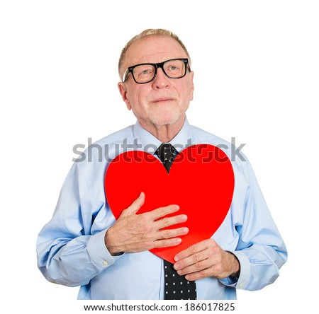 Closeup portrait, happy smiling, senior mature man looking upwards, holding large red heart to chest daydreaming of women in love, isolated white background. Positive emotion facial expression feeling - stock photo