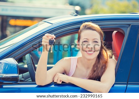 Closeup portrait happy, smiling, young attractive woman, buyer sitting in her new blue car showing keys isolated outside dealer, dealership lot office. Personal transportation, auto purchase concept - stock photo