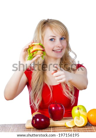 Closeup portrait happy smiling young, fit female holding, eating vitamin fruit sandwich, burger made of apples oranges strawberries fruits pointing at you isolated white background. Healthy lifestyle