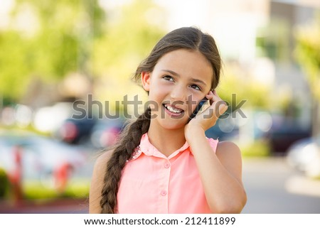 Closeup portrait, happy teenage girl talking on cell, mobile phone, isolated outdoors, outside background. Positive human emotions, facial expressions, life perception, communication concept - stock photo