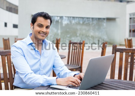 Closeup portrait, happy young handsome man in blue shirt typing away, browsing digital computer laptop, isolated background of sunny outdoor, waterfall, brown chairs, office background - stock photo