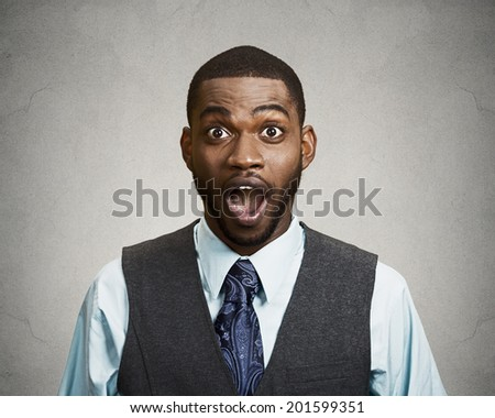 Closeup portrait happy young man, wide open mouth looking shocked, surprised in full disbelief isolated black grey background. Positive human emotions, facial expressions, feeling, attitude, reaction - stock photo