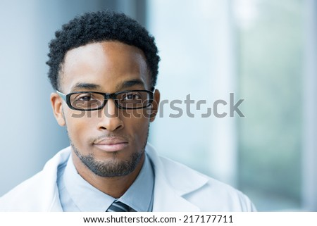 Closeup portrait head shot of friendly, smiling confident male doctor, healthcare professional with a white coat, black glasses, isolated hospital clinic background. - stock photo