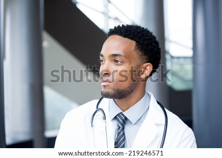 Closeup portrait head shot of friendly, smiling confident male doctor, healthcare professional with a white coat and stethoscope, looking away to side, isolated hospital clinic background. - stock photo