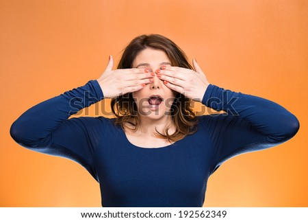 Closeup portrait, head shot young, coy woman, female closing eyes with hands can't see, hiding, mouth open, isolated orange background. See no evil concept. Negative emotion, facial expression feeling - stock photo