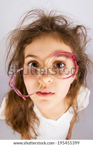 Closeup portrait, headshot confused funny looking little girl with messed up glasses, hair scared, isolated grey background. Human emotions, facial expressions, reaction, feelings, life perception - stock photo
