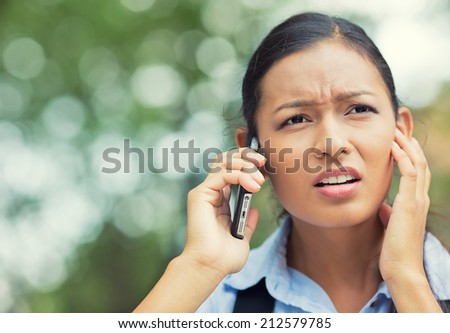Closeup portrait, headshot frustrated young businesswoman talking on mobile phone, touching face, closing ear with hand while standing outdoors, bad news, cellular connection concept. Negative emotion - stock photo