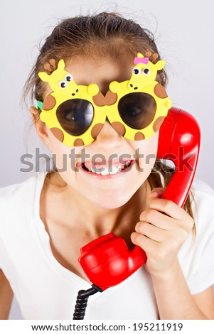 Closeup portrait, headshot happy, funny looking little girl with sun glasses speaking, talking on phone isolated grey background. Positive human face expressions, emotions, feelings, life perception - stock photo