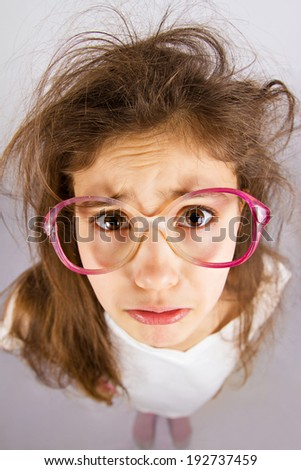 Closeup portrait, headshot little sad girl with glasses, scared, afraid, about to cry, isolated grey background. Negative human emotions, facial expressions, reaction, feelings, life perception - stock photo