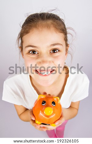 Closeup portrait, headshot, little, smiling, funny looking girl holding, saving money in piggybank, isolated white, grey background. Positive facial expressions, emotions, clever  financial decisions