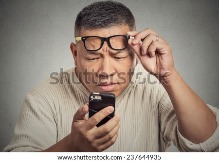 Closeup portrait headshot middle aged man with glasses having trouble seeing cell phone screen because of vision problems. Bad text message. Negative human emotion facial expression feeling perception - stock photo