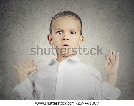 Closeup portrait headshot scared child, boy hands up in air, opened mouth looking at you camera, isolated grey wall background. Human facial expressions, emotions, feelings, body language, perception - stock photo