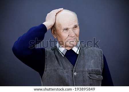 Closeup portrait, headshot senior, elderly, mature man, old sad worker, hand on head, looking troubled, deep thought, thinking, isolated blue background. Human emotions, facial expressions, reaction - stock photo