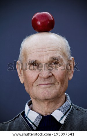 Closeup portrait, headshot senior man, grandfather, old guy with apple on his head, isolated, blue, black background. Geriatrics, longevity, healthy dieting, health. Human face expressions, emotions - stock photo