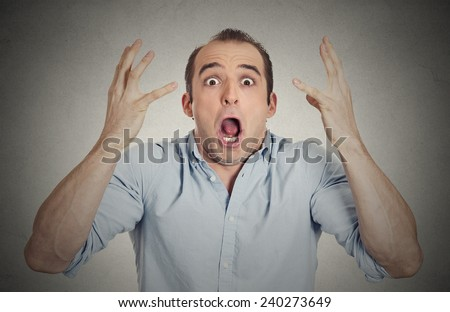 Closeup portrait headshot shocked stunned surprised young man eyes mouth wide open, hands in air yelling screaming shouting isolated grey wall background. Negative emotion facial expression feeling - stock photo