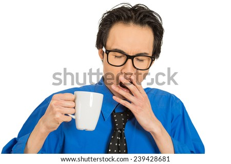 Closeup portrait headshot tired falling asleep young businessman holding cup of coffee, struggling not to crash stay awake, keeping his eyes opened, isolated white background. Lack of sleep concept - stock photo