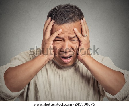 Closeup portrait headshot upset, stressed out, sick, tired middle aged man having headache, bad day at work isolated grey wall background. Negative human emotions, facial expressions, life crisis - stock photo