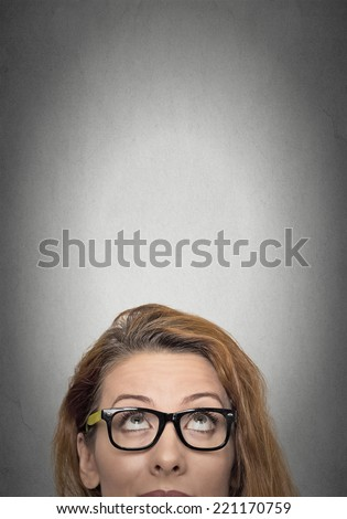 closeup portrait headshot woman looking up grey wall background with copy space above head. Human face expressions, emotions, feelings, body language