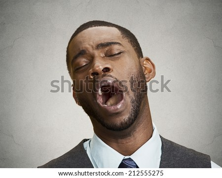 closeup portrait, headshot young bored man, yawning isolated grey wall background. Facial expressions, feelings, body language. Long working hours, chronic fatigue of corporate executive - stock photo