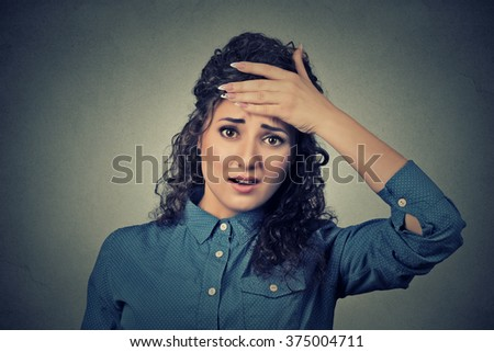Closeup portrait headshot young business woman looking shocked, surprised, hand on head stressed realized mistake isolated grey wall background. Negative emotion facial expression feeling reaction - stock photo