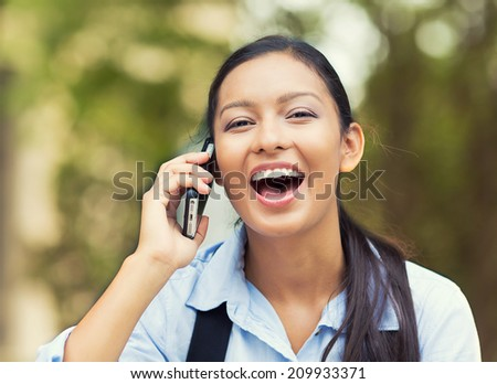 Closeup portrait, headshot young, happy beautiful woman laughing, speaking on cell phone, isolated outdoors background of park trees. Positive human emotion, facial expression, feeling life perception - stock photo