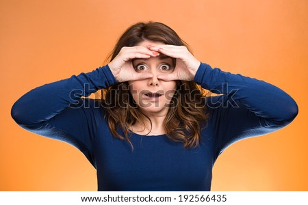Closeup portrait, headshot young, middle aged curious woman, peeking, surprised shocked through fingers like binoculars searching something, looking future, isolated orange background. Face expression - stock photo