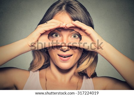 Closeup portrait, headshot young stunned curious woman, peeking looking through fingers like binoculars searching something isolated on gray wall background. Face expression reaction  - stock photo