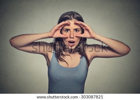 Closeup portrait, headshot young woman, peeking through fingers like binoculars  surprised shocked searching something looking into future isolated gray wall background. Human face expression emotion  - stock photo