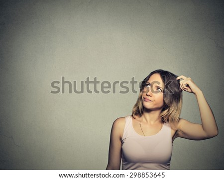 Closeup portrait headshot young woman scratching head, thinking daydreaming deeply about something looking up isolated on gray wall background. Human facial expression emotion feeling sign symbol - stock photo