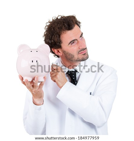 Closeup portrait, health care professional, scientist,  pharmacist, doctor, nurse knocking on piggy bank, listening to see if there is money, isolated on white background. Health care reform - stock photo
