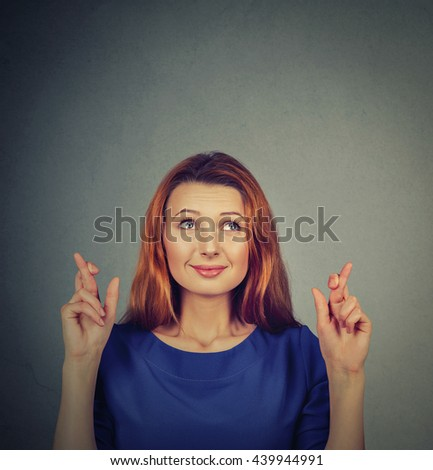 Closeup portrait hopeful beautiful woman crossing her fingers, eyes closed, hoping, asking best isolated on gray wall background. Human face expression, emotions, feeling attitude reaction - stock photo