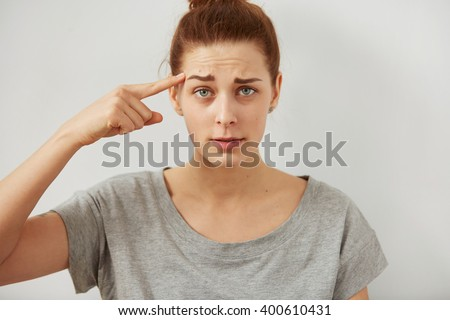Closeup portrait indignant young freelancer woman looking at camera holding  finger at head with disgusting emotion on her face isolated grey wall background. Human emotion, reaction, expression. - stock photo