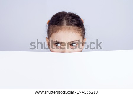 Closeup portrait little girl, looking surprised, scared, cautious, curious, hiding behind blank white paper billboard, blank sign, space for text looking side way isolated black background. Expression - stock photo