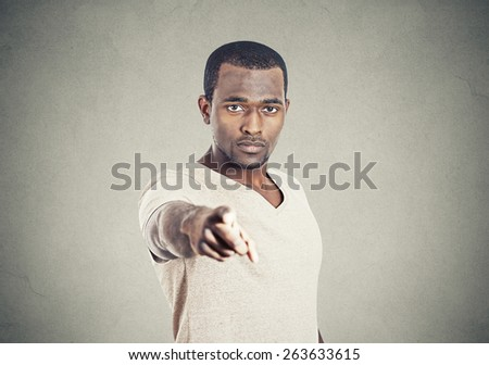 Closeup portrait man pointing at you with index finger isolated on grey wall background.  - stock photo
