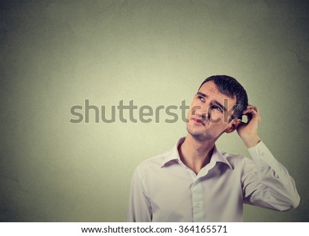 Closeup portrait man scratching head, thinking deeply about something, looking up, isolated on grey wall background. Human facial expression, emotion, feeling, sign body language - stock photo