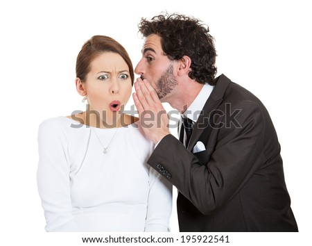 Closeup portrait man whispering into woman ear telling her something secret, disturbing, slander. Shocked, surprised, disgusted, annoyed mad response. Negative human emotion, facial expression feeling - stock photo