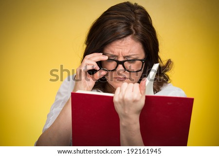 Closeup portrait, mature woman with black eye glasses trying to read book, having difficulties seeing text because vision problems. Negative emotion facial expression feelings reaction, health issues - stock photo