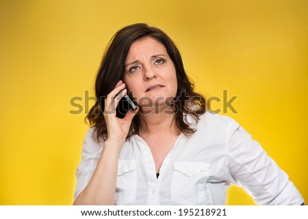 Closeup portrait middle aged angry business woman, corporate employee talking on cell phone, having unpleasant conversation, isolated yellow background. Negative emotions, facial expressions, reaction - stock photo