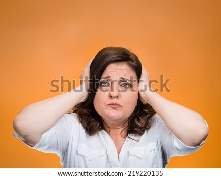 Closeup portrait middle aged annoyed unhappy stressed woman covering ears looking up stop making loud noise giving me headache isolated orange background. Negative emotion, reaction, face expression - stock photo