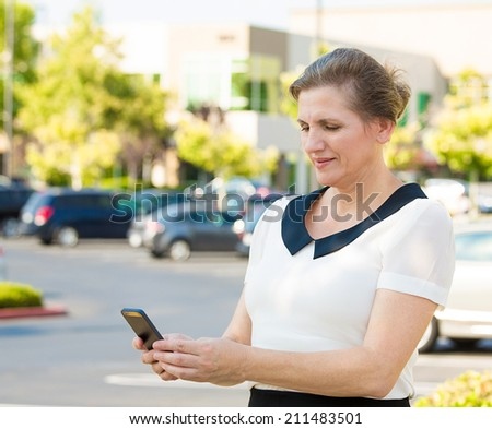 Closeup portrait middle aged, happy woman texting on her smart phone, isolated outdoor, outside background. Communication, connection concept. Positive facial expressions, emotion, feelings, good news - stock photo