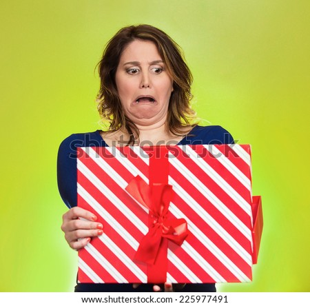 Closeup portrait middle aged woman opening gift box very upset at what she received, isolated green background. Negative human emotion, facial expression. Unsuccessful holiday shopping concept - stock photo